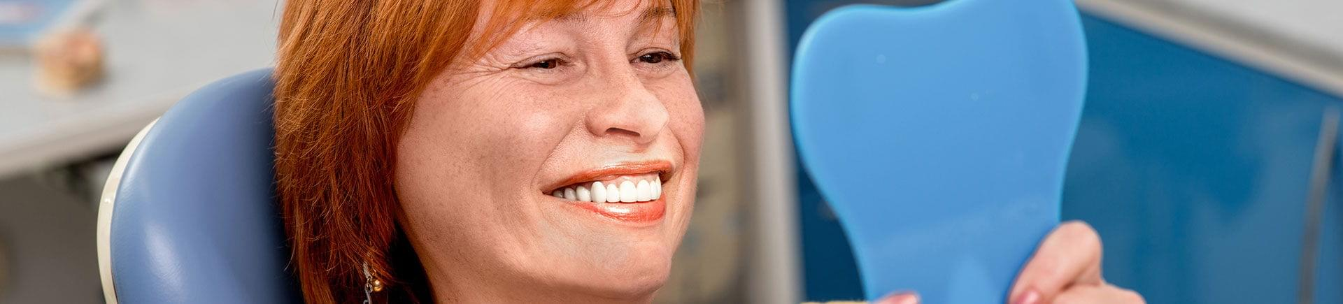 Happy mature woman in a dental chair looking at her perfect teeth in a mirror.