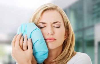 Woman with dental pain pressing a cold compress to her cheek.