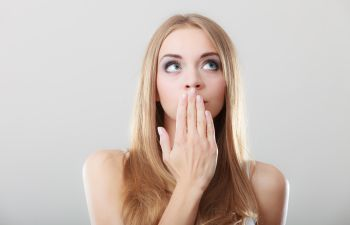 A young woman covering her mouth with her hand because of bad breath.
