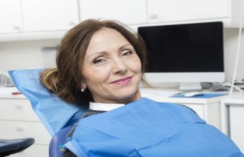 A relaxed satisfied woman in a dental chair.