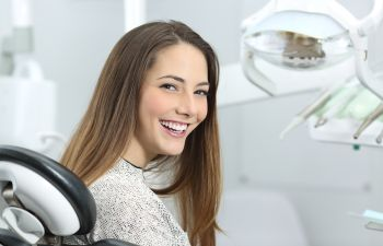 Smiling young woman in a dental chair.