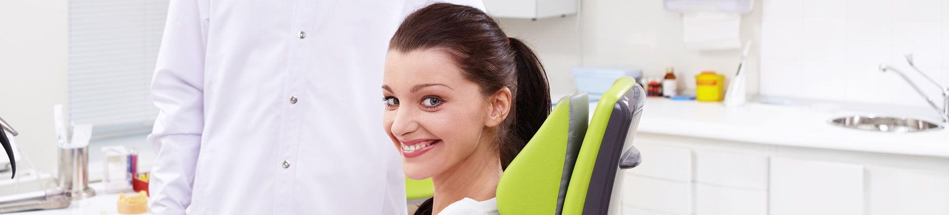 A happy young woman with perfect smile sitting in a dental chair .
