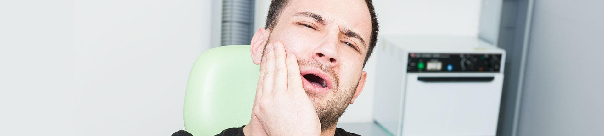 A man suffering from severe tooth pain.