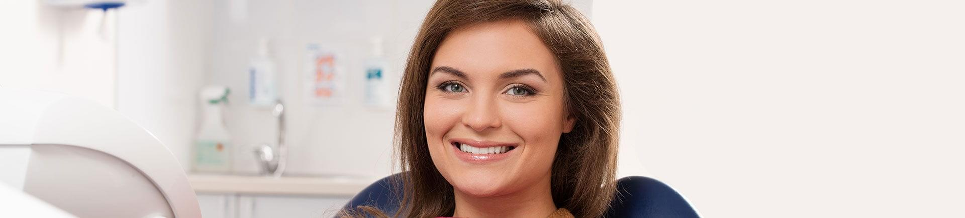 A cheerful young woman with a perfect smile at a dental appointment.