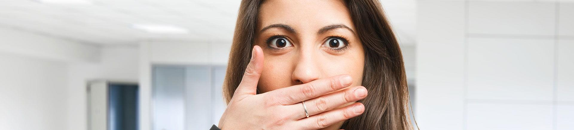 A young woman covering her mouth with her hand due to bad breath.