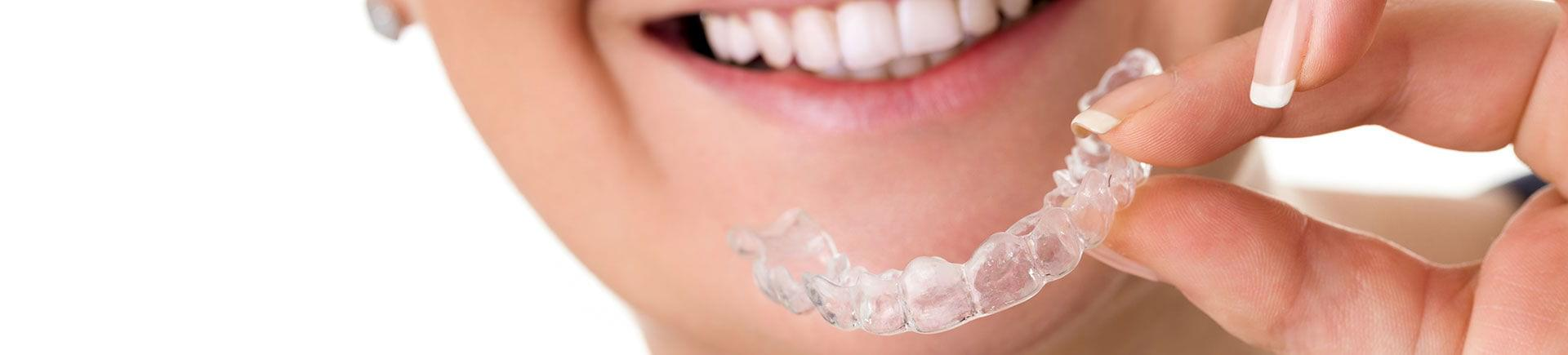 A woman holding an Invisalign aligner .