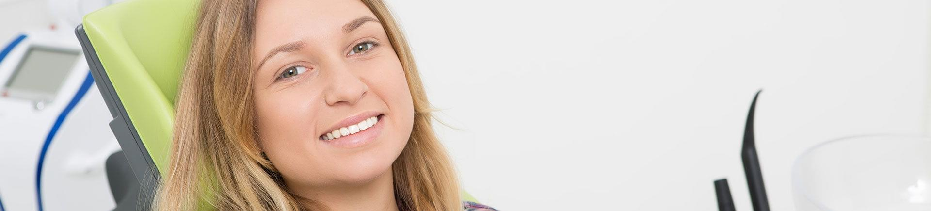 A happy young woman with a perfect smile after dental veneers treatment.