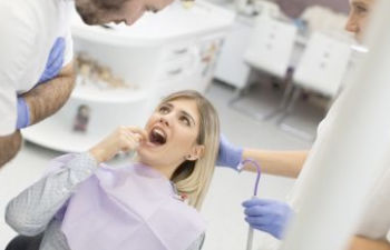 A young woman during a dental appointment showing the problem area to the dentist.